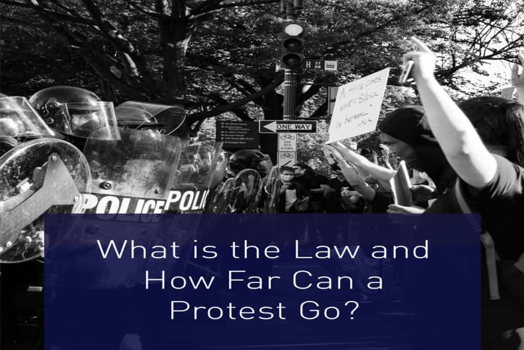 """Protestors facing police officers who are wearing riot gear with graphic text overlay that says, """"What is the law and how far can a protest go?"""""""