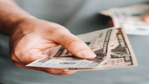 A male's hand holding paper bills