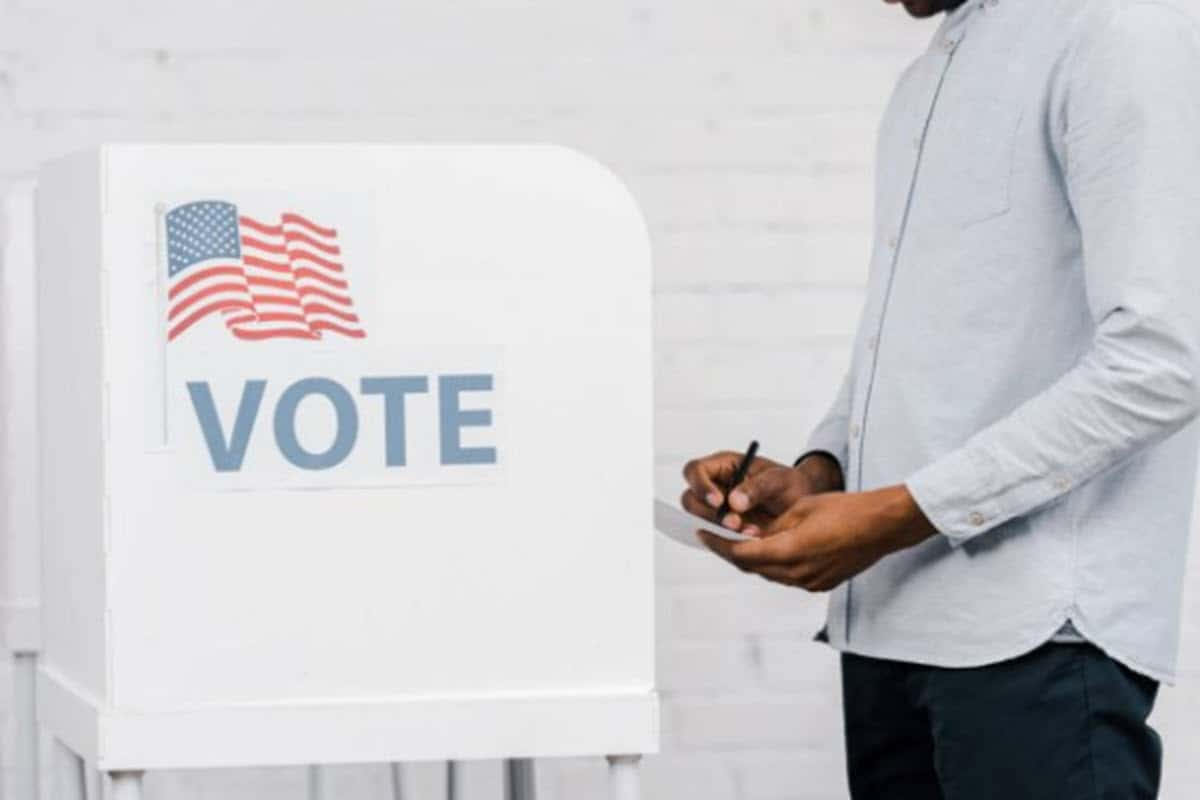 Man standing in front of voting booth with a pen and a ballot in his hand.