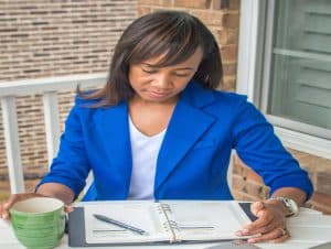 Shenetta Webster sitting outside and reading her Daily One planner which is opened up on a table.