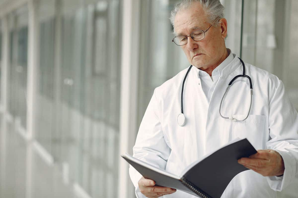 Doctor, wearing a lab coat and stethoscope, is standing in the hallway reading a file.