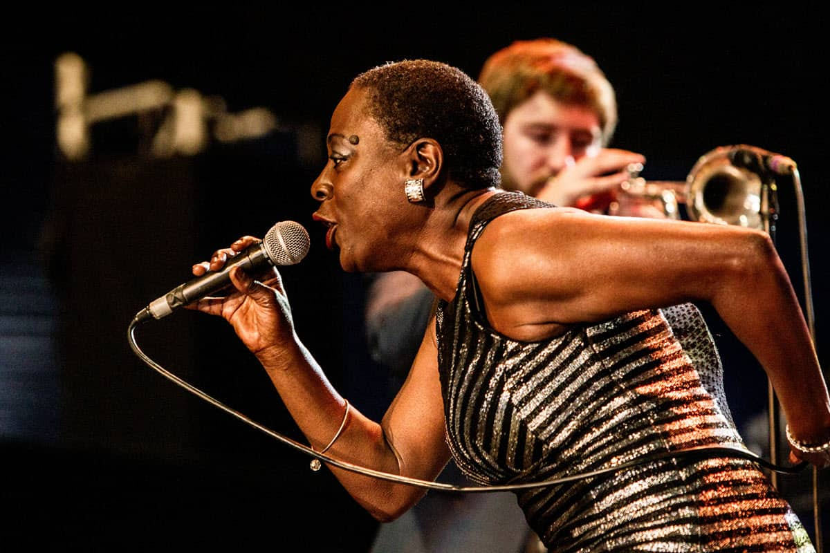 Woman on stage singing into a microphone with a trumpet player in the background.