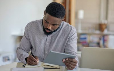 Man working at home using Daily One Method in Always Satisfied Planner, 400x266